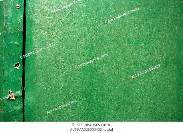 Green painted surface with holes, close-up, full frame