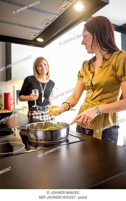 Smiling women preparing food in kitchen