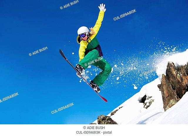 Young female snowboarder jumping