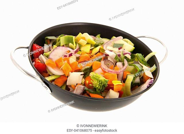 Mixed raw vegetables in frying pan isolated over white background