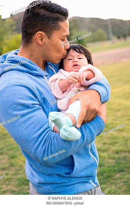 Father cradling and kissing baby in park