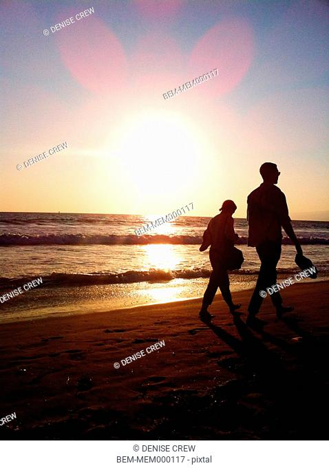 Silhouette of couple walking on beach at sunset