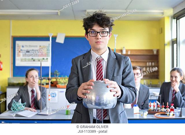 Portrait high school student touching electrostatic generator in science class