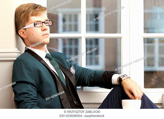young handsome fashion model stylish man relaxing thinking and waiting in a cafe / restaurant with coffee