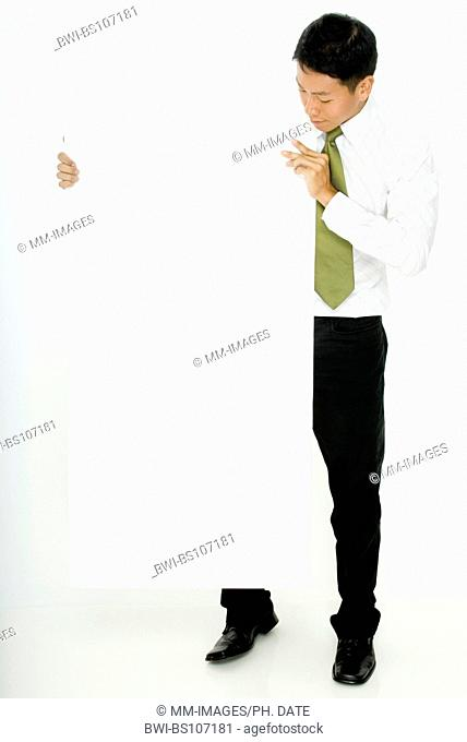 young Asian businessman looking at a large blank white sign, he is holding