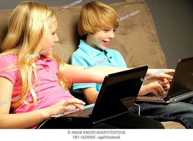 A picture of two siblings using laptop computers on a couch