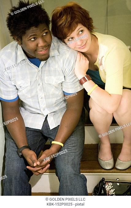Elevated view of a young inter-racial couple sitting on stairs
