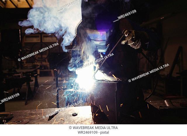 Welder cutting metal in workshop