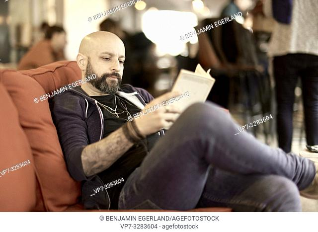 man reading book in cafe, Paris, France