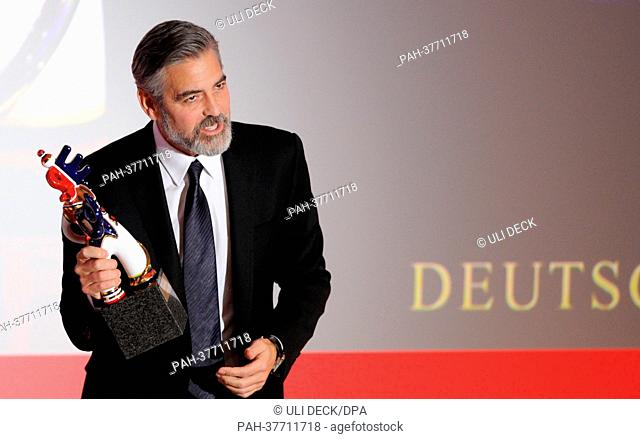 US actor George Clooney holds the award after receiving the German Media Prize 2012 at the award ceremony with Karlheinz Koegel of Media Control in Baden-Baden