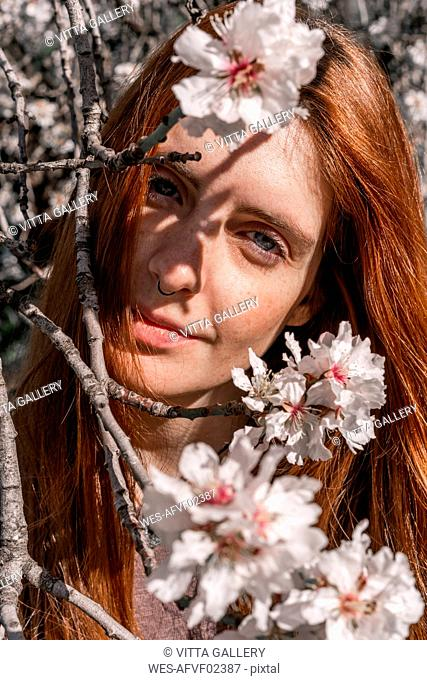 Portrait of redheaded woman behind twigs of blossoming tree