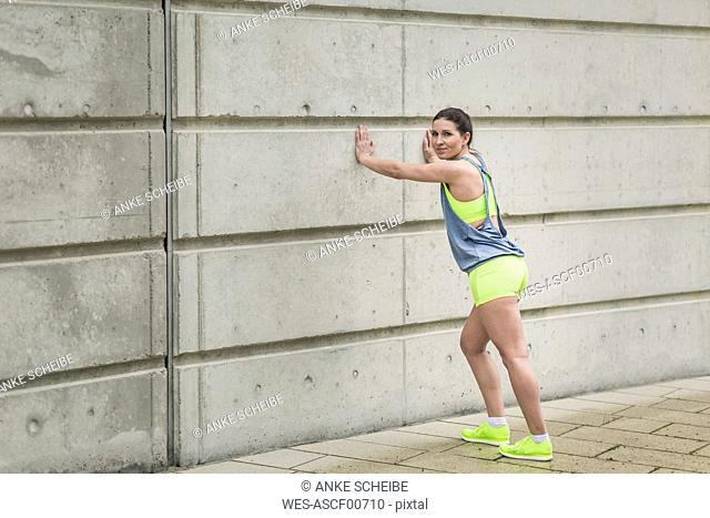 Woman stretching at building