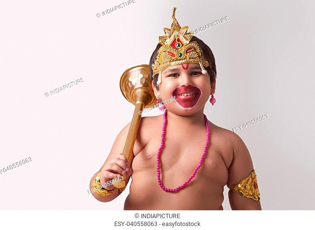 Portrait of smiling boy dressed as God Hanuman against white background