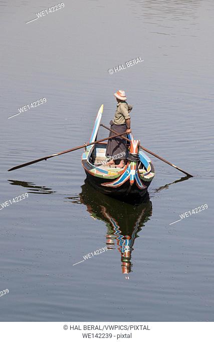 Boatman waits to row tourists around Taungmyo Lake. Amarapura, Myanmar