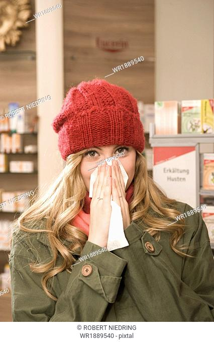 Woman In Pharmacy Blowing Nose, Munich, Bavaria, Germany
