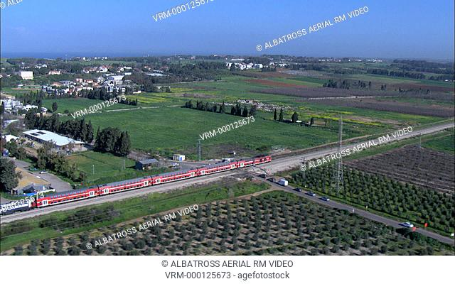 Aerial footage of a red train crossing rural areas; fields and orchards; small country towns and settlements