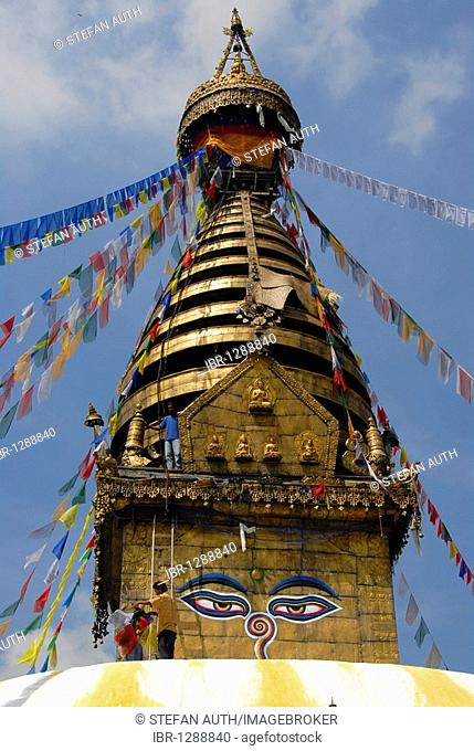 UNESCO World Heritage Site, Tibetan Buddhism, architecture, Bodhnath Stupa, Boudhanath, Boudha, two eyes looking down, men hanging up on colorful prayer flags