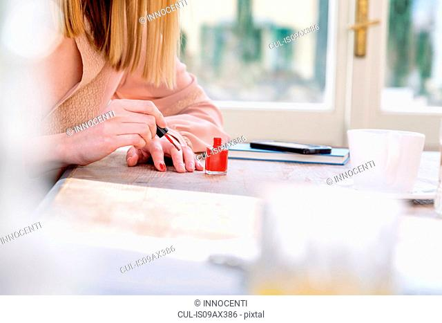 Cropped view of woman painting nail with red nail varnish