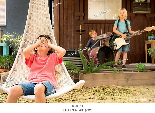 Girl in hanging chair, hands on head and children playing guitar and drums in band