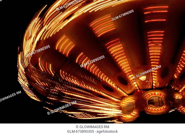 Close-up of a carousel spinning at night