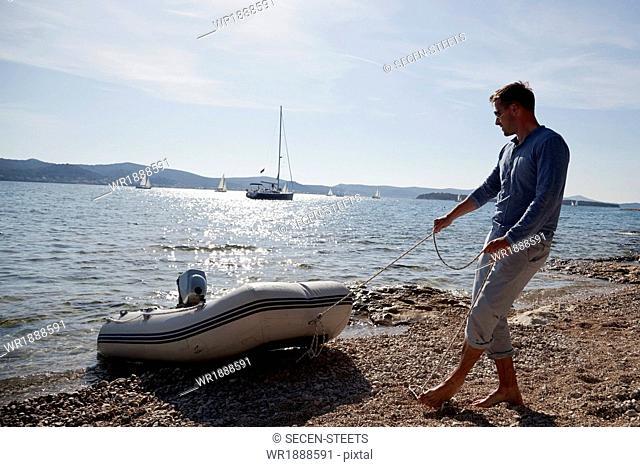 Man pulling dinghy on beach, Dalmatia, Croatia, Europe