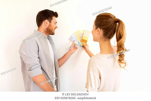 repair, people and interior design concept - happy couple with color samples palettes at new home