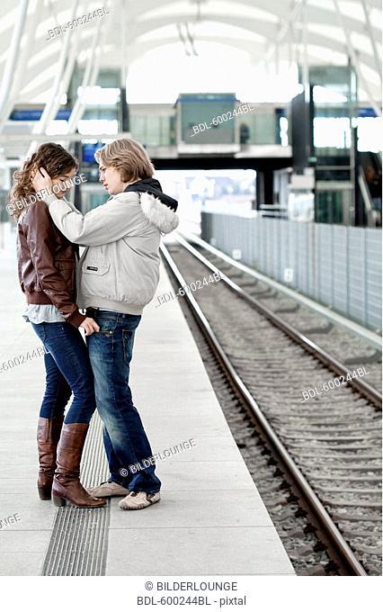 sad teenage couple embracing at station