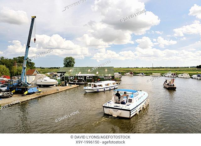 Pleasure boats and services on the River Ant in the Norfolk Broads, England. Looking south east from Ludham Bridge. Summer