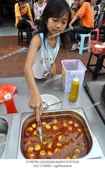 Malacca (Malaysia): a girl serving 'fish balls' in a Chinatown's street stall