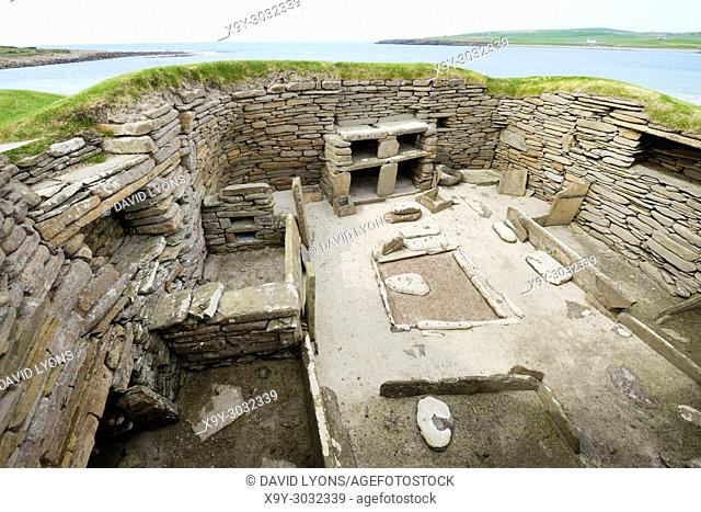 Skara Brae Stone Age Neolithic village at Skaill, Orkney, Scotland. Interior, box beds, hearth and dresser 3100 BC. House 1 with Bay of Skaill behind