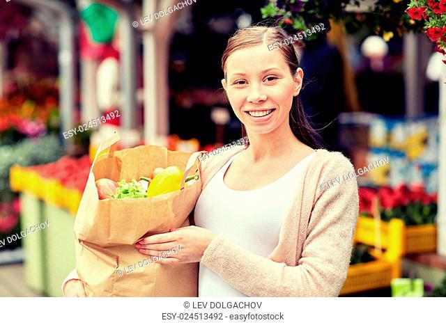 sale, shopping and people concept - happy woman with paper bag full of food at street market