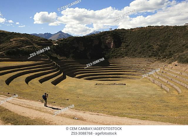 Tourist walking on the terraces at Moray Ruins of the ancient Inca empire, Cusco Region, Peru, South America