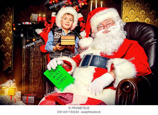Santa Claus and laughing cute boy sitting in Christmas room with gifts. Christmas home d?cor