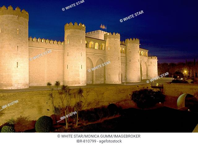 Palacio de Aljaferia palace illuminated at night under floodlights, flags flying over external wall and towers, Moorish architecture, Zaragoza, Saragossa