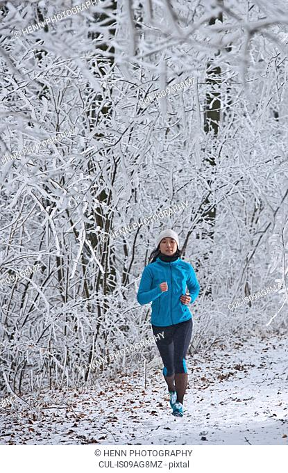 Mature woman jogging in forest in winter snow