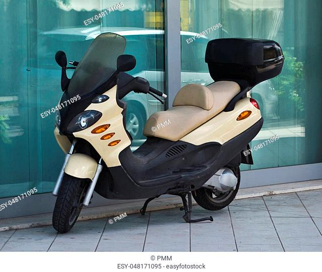futuristic scooter with light brown trunk parked on the sidewalk