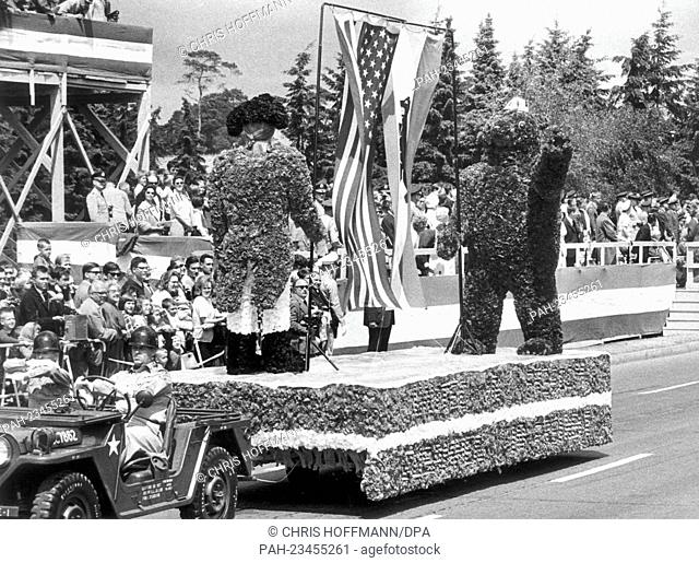 A show car with the Berlin Bear and a US soldier of the independence war made of flowers and plants driving past a VIP stand during a parade on occasion of the...