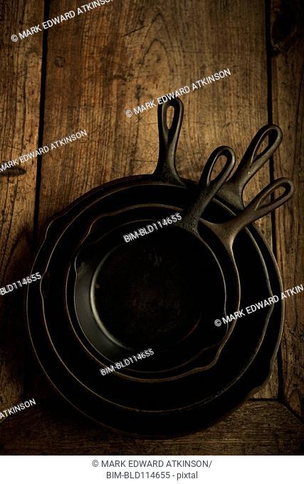 Empty cast iron pans on wooden board