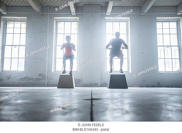 Silhouette of athletes jumping on platforms