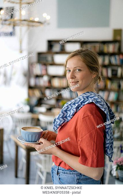 Portrait of smiling young woman serving coffee in a cafe
