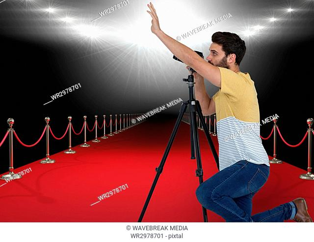 photographer taking a photo in the red carpet with stadium lights on back