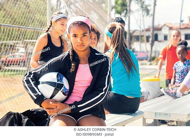 Portrait of schoolgirl amongst group holding soccer ball on school sports field