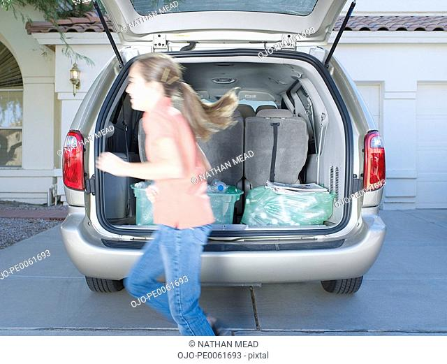 Young girl outdoors running by van with recyclable materials in the back