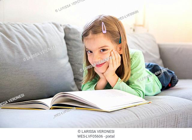 Portrait of smiling little girl lying on couch with a book