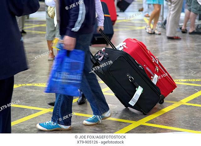 male and female passengers pull wheeled luggage with flight tags on out of Reina Sofia Sur TFS South Airport Tenerife Canary Islands Spain