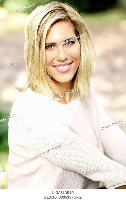 Portrait of smiling blond woman wearing knit pullover