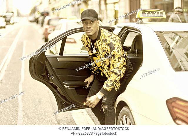 young stylish man getting out of taxi, exiting car, at city street, upper-class life, in Munich, Germany