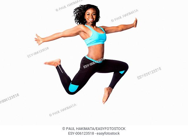 Beautiful happy energetic woman doing freedom sports jum with arms open, isolated