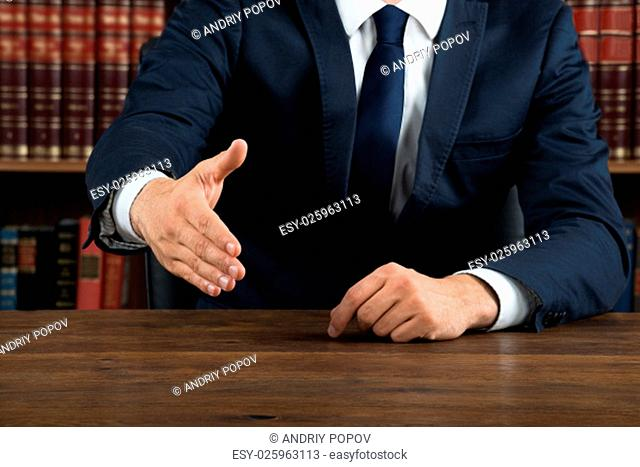 Midsection of lawyer offering handshake while sitting at desk in courtroom