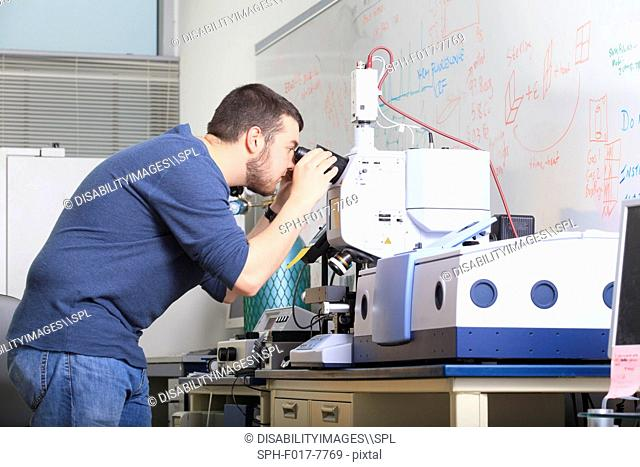 Engineering student looking through optical microscope on chemical analysis equipment in a laboratory